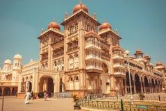 Slott av Mysore som byggs för kungafamiljen i 1912 och några turister Fotografering för Bildbyråer