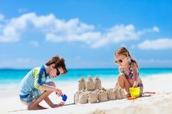 Två ungar som leker på stranden arkivfoton