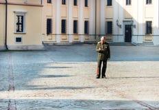 Slott 2, Nesvizh Vitryssland på mars 11, 2015 Nesvizh slott En man i likformig och en mobiltelefon i hans hand Royaltyfri Bild