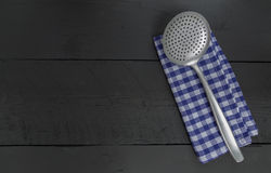 Slotted spoon and dish cloth on black wooden background Stock Photography