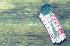 Slotted spoon and kitchen towel on rustic wooden background Stock Photos