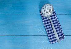 Slotted spoon and tea towel on blue wooden background Stock Photography