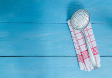 Slotted spoon and tea towel on blue wooden background Royalty Free Stock Image