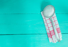 Slotted spoon and tea towel on turquoise wooden background Stock Photo