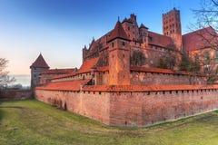 Slotten av den Teutonic beställningen i Malbork på solnedgången Arkivfoto