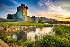 Slotten fördärvar med en sjö och gräs på solnedgångapelsinhimlen arkivfoto