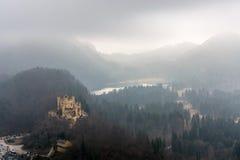 Slotten Hohenschwangau och sjön Alpsee på en dimmig dag Arkivfoto