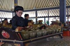 Slotttjänare som utför traditionella musikinstrument, kallade Gamelan under en stor gazebo royaltyfri bild