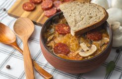 Slovak Christmas national cabbage soup in ceramic bowl with sausage on the tablecloth background.  royalty free stock image