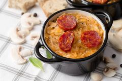 Slovak Christmas national cabbage soup in small black pot with sausage on the tablecloth background.  stock photo