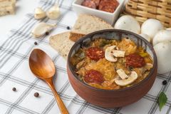 Slovak Christmas national cabbage soup in small black pot with sausage on the tablecloth background.  stock photos