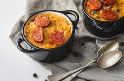 Slovak Christmas national cabbage soup in two small black pots with sausage on the tablecloth background.  royalty free stock photo
