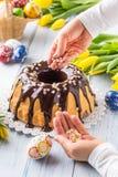 Slovak och tjeckisk kakababovka för läcker ferie med chokladglasyr Kvinnliga händer som dekorerar en kaka Påskgarneringar - vår royaltyfria foton