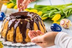 Slovak och tjeckisk kakababovka för läcker ferie med chokladglasyr Kvinnliga händer som dekorerar en kaka Påskgarneringar - vår arkivfoto