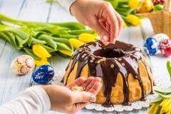 Slovak och tjeckisk kakababovka för läcker ferie med chokladglasyr Kvinnliga händer som dekorerar en kaka Påskgarneringar - vår fotografering för bildbyråer