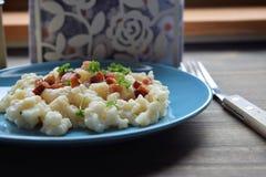 Slovak traditional potato gnocchi with sheep cheese and bacon,wooden table. Slovak traditional potato gnocchi with sheep cheese and bacon royalty free stock images