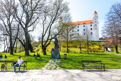 Slovakia, Bratislava - April 14, 2018: Medieval castle park on hill above the Danube river. Park in foreground with young peoples stock images