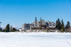 Slovakia: Strbske pleso resort, view of frozen lake in winter and hotel resort above. Blue sky. stock photography