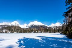 Slovakia, Strbske Pleso: View of frozen lake in Big Tatra, Slovakia. Mountains in background, the trees and lake in foreground. Wi royalty free stock image