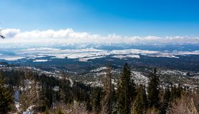 Slovakia: View of small tatra nizke tatry from the Strbske Pleso. Mountains panorama in far, trees in foreground. Beautiful far. Look royalty free stock photo