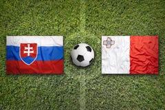Slovakia vs. Malta flags on soccer field. Slovakia vs. Malta flags on a green soccer field Royalty Free Stock Image