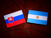 Slovakian flag with Argentinian flag on a tree stump  Stock Images