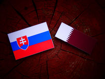 Slovakian flag with Qatari flag on a tree stump isolated. Slovakian flag with Qatari flag on a tree stump Stock Image