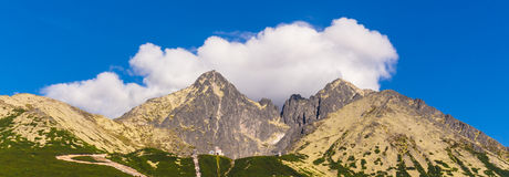 Slovakian Tatras. Lomnicky peak on the background of clouds and blue sky. Stock Photos