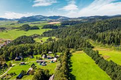 Slovakian town on forested hillside in summer. Slovakian town Stara Lubovna on forested hillside. beautiful rural scenery in mountainous area viewed from above Royalty Free Stock Image