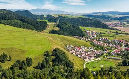 Slovakian town on grassy hillside in summer. Slovakian town Stara Lubovna on grassy hillside. beautiful rural scenery in mountainous area viewed from above on a Royalty Free Stock Photo