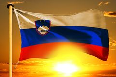 Slovenia flag weaving on the beautiful orange sunset with clouds background. Slovenia flag weaving on the beautiful orange sunset background stock images