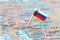Slovenia map and flag pin. Paper flag pin of Slovenia on a country map showing neighboring countries. Officially the Republic of Slovenia, it is a nation state Royalty Free Stock Images