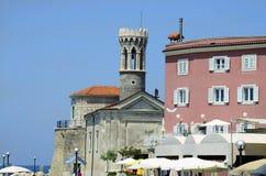 Slovenia, Piran. Piran, Slovenia - church S. Clemente aka Marija Zdravja and colorful buildings in the pictoresque village on Adriatic sea Stock Image