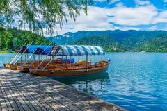 Slovenia Pletna Tradycyjna łódź czekać na ciebie przy Krwawić jeziorem zdjęcia stock