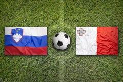 Slovenia vs. Malta flags on soccer field. Slovenia vs. Malta flags on a green soccer field Stock Photography