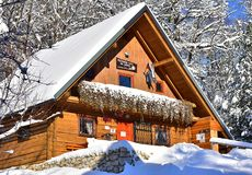 Slovenian chalet in winter covered with snow. Slovenian wooden cabin in winter covered with snow. It`s called Pečovniška koča on hill Grmada. Celje, Slovenia Stock Photography
