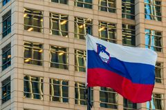Slovenian flag on the background of office building, Atlanta, USA. The flag of Slovenia closeup on the background of facade of office skyscraper, Atlanta, USA Stock Photos