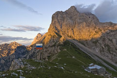 Slovenian flag in high mountains enviroment. With view on mountain hut stock photography
