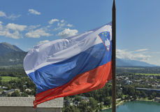 Slovenian national flag over Lake Bled and town. Slovenian national flag fluttering over Lake Bled and town Royalty Free Stock Photos