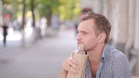 Slovenly man drinking alcohol in the street. beer in a paper bag. stock video footage