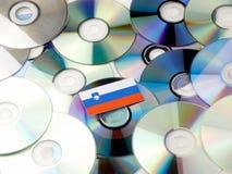 Slovensk flagga överst av CD- och DVD-högen som isoleras på vit Royaltyfri Fotografi