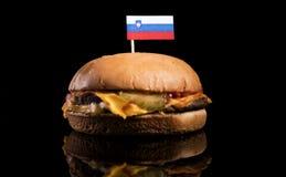 Slovensk flagga överst av hamburgaren på svart Arkivbild