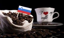 Slovensk flagga i en påse med kaffebönor på svart Royaltyfria Bilder