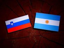 Slovensk flagga med den argentinska flaggan på en trädstubbe Arkivbilder