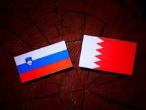 Slovensk flagga med den bahrainska flaggan på en trädstubbe Royaltyfri Bild