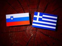 Slovensk flagga med den grekiska flaggan på en isolerad trädstubbe Royaltyfria Bilder