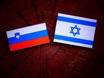 Slovensk flagga med den israeliska flaggan på en trädstubbe Fotografering för Bildbyråer