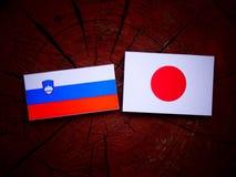 Slovensk flagga med den japanska flaggan på en isolerad trädstubbe Arkivfoton
