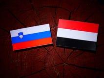Slovensk flagga med den jemenitiska flaggan på en isolerad trädstubbe Royaltyfri Bild