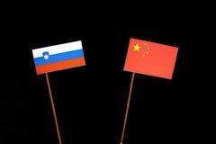 Slovensk flagga med den kinesiska flaggan på svart Arkivfoto